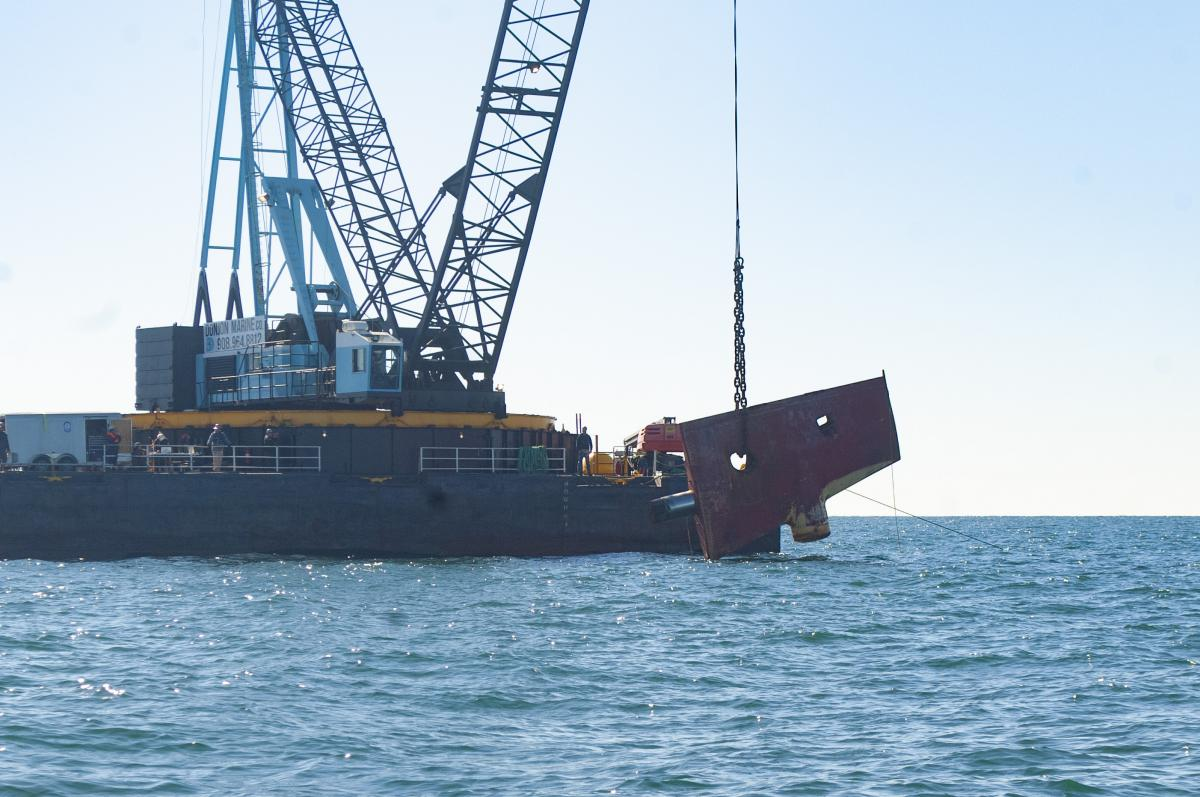 Rudder is lowered into water by crane