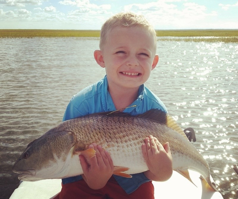 Picture of a young child holding a large tagged red drum.