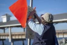 : Elizabeth Cheney, a beach water quality manager with the Coastal Resources Division of the Georgia Department of Natural Resources, tends to a beach advisory sign near Pier Village on St. Simons Island.